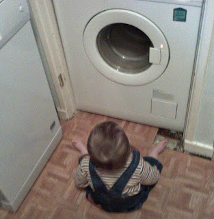 Baby Sitting on Floor Avidly Watching the Washing Machine