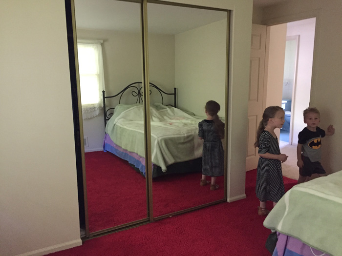 upstairs bedroom with red carpet and mirrored closet doors