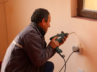 Bekir starts drilling holes to fix it in place