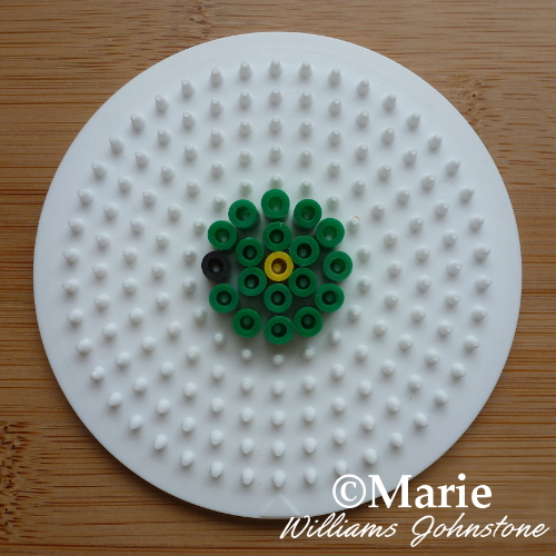 Green and yellow beads Hama Perler on round pegboard