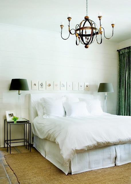 Bedroom with a white slipcovered headboard, green floor length curtains, tile floor and a brass chandelier