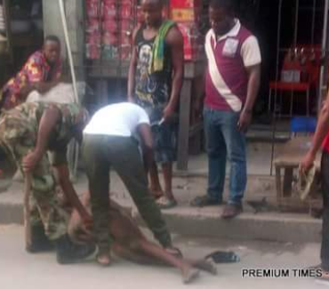 Photos: Two soldiers caught on camera beating a commercial tricycle rider in Lagos after stripping him naked, threatens to cut off his penis