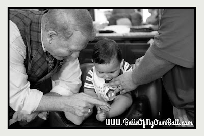 A photo of a baby being tickled while receiving his first haircut at Harmony Barber Shop in the Magic Kingdom.