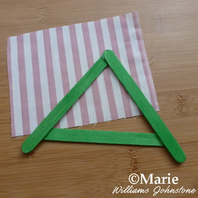 green triangular roof made with wooden sticks and fabric