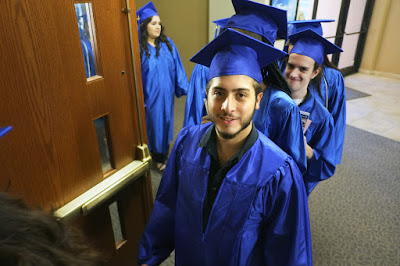 Image of an HSE grad smiling at the camera, in processional lineup.