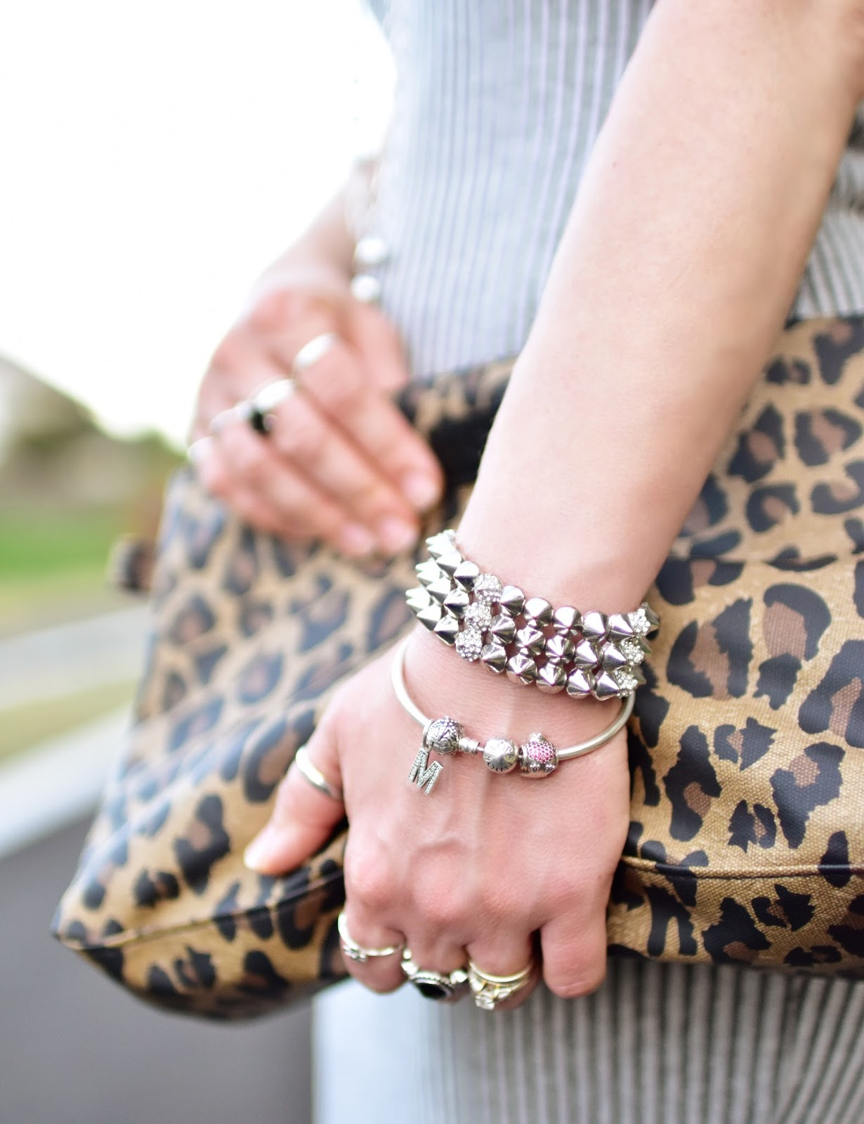 leopard-patterned clutch, stacked bracelets and rings