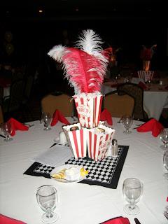 Centro de mesa hecho con cajas de pop corn y plumas.