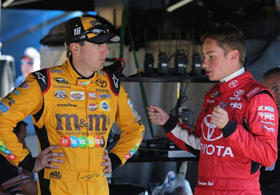 Christopher Bell, driver of the #4 JBL Toyota, talks with Kyle Busch, driver of the #18 M&M's Halloween Toyota, during practice