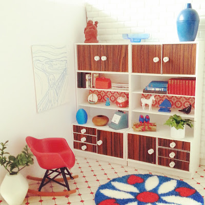 One-twelfth scale miniature retro lounge with white walls, woodgrain and white display units, red Eames rocking chair and a round retro rug in colours of red, teal and white on the floor.