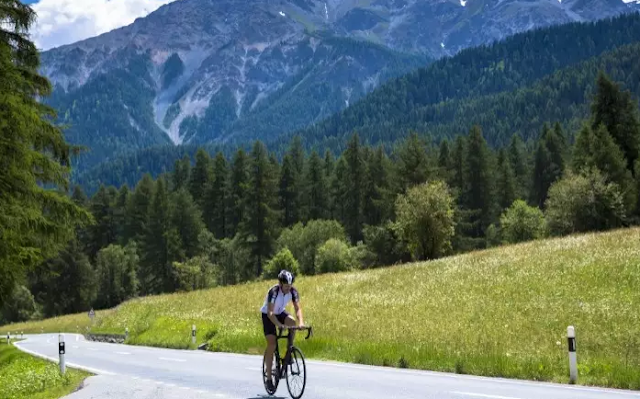 A Cyclist On The Road Of Switzerland Top 10 World's Happiest Countries 2017