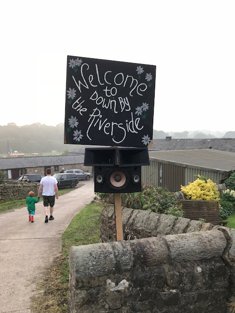 A sign reading welcome to the Down By The River Festival against a farm setting and a father and son walking in the distance.