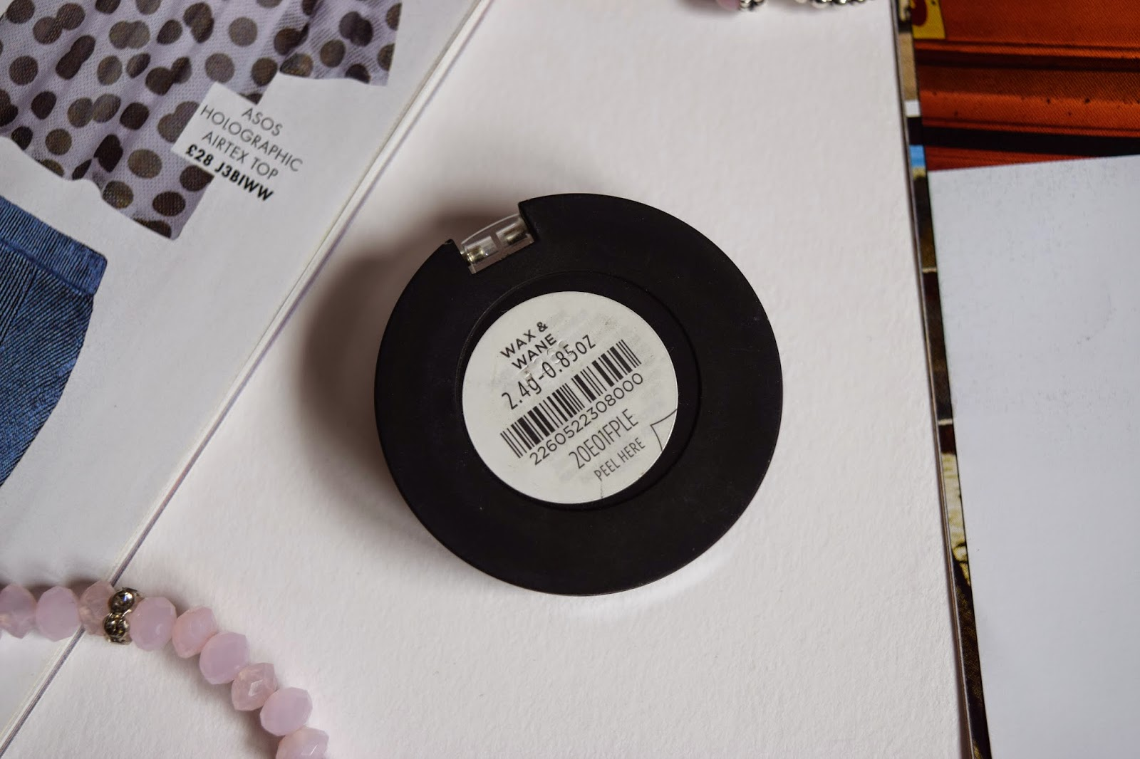 THE BOTTOM OF THE EYESHADOW SINGLE WITH A LABEL THAT READ 'WAX & WANE