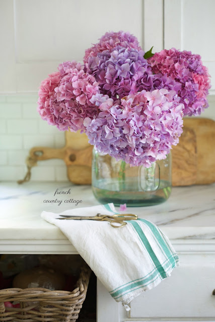 marble kitchen and blue glass vase of flowers