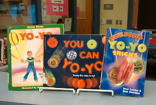 Three books about Yo-Yos arranged upright on wire stands atop library counter with their covers facing outward. From left to right the books are, 'Yo-Yos: Tricks to Amaze Your Friends,'  'You Can Yo-Yo' and 'Awesome Yo-Yo Tricks.'