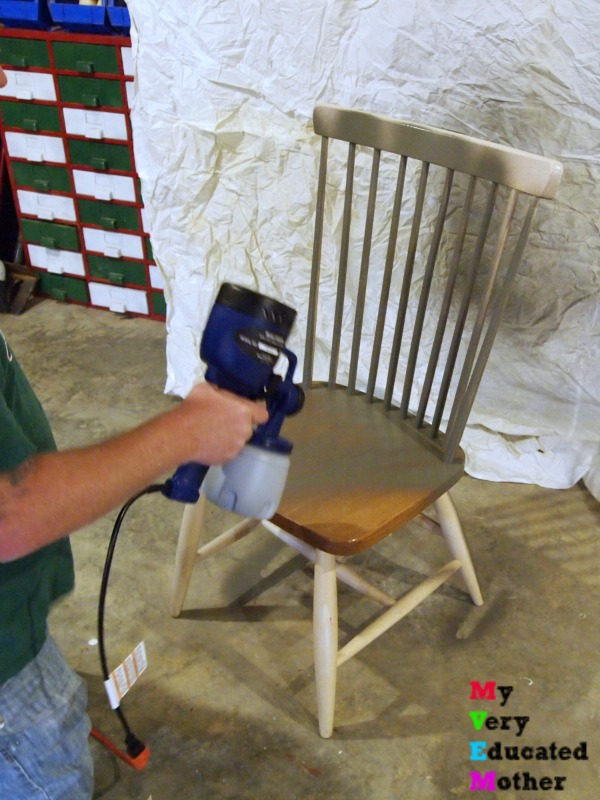 Using a paint sprayer to paint chairs.