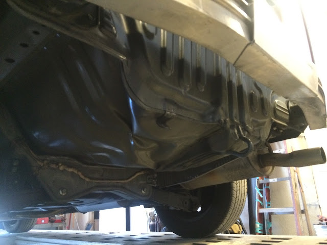 Looking at underside of car after bumper cover removed. There are large dents in floor and rear panel.