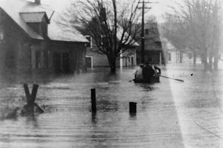 A black and white photograph of a flooded street. A few figures are seated in a boat, paddling through the water.