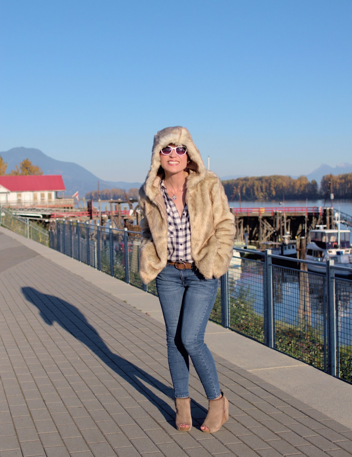 Monika Faulkner outfit inspiration - faux-fur hoodie, plaid flannel shirt, skinny jeans, open-toe booties, and white sunglasses