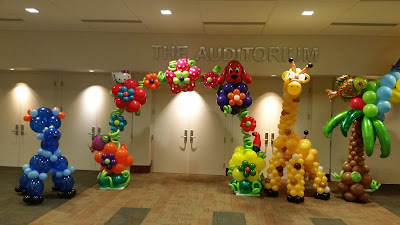 Tropical themed balloon sculptures with dog, giraffe, balloon arch, palm tree, balloon animals