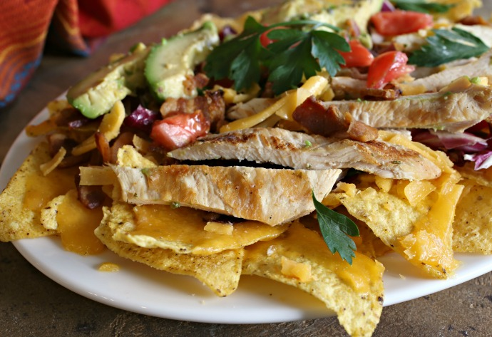 Tortilla chips topped with cheddar cheese, crumbled bacon, diced tomatoes, avocado and grilled chicken.