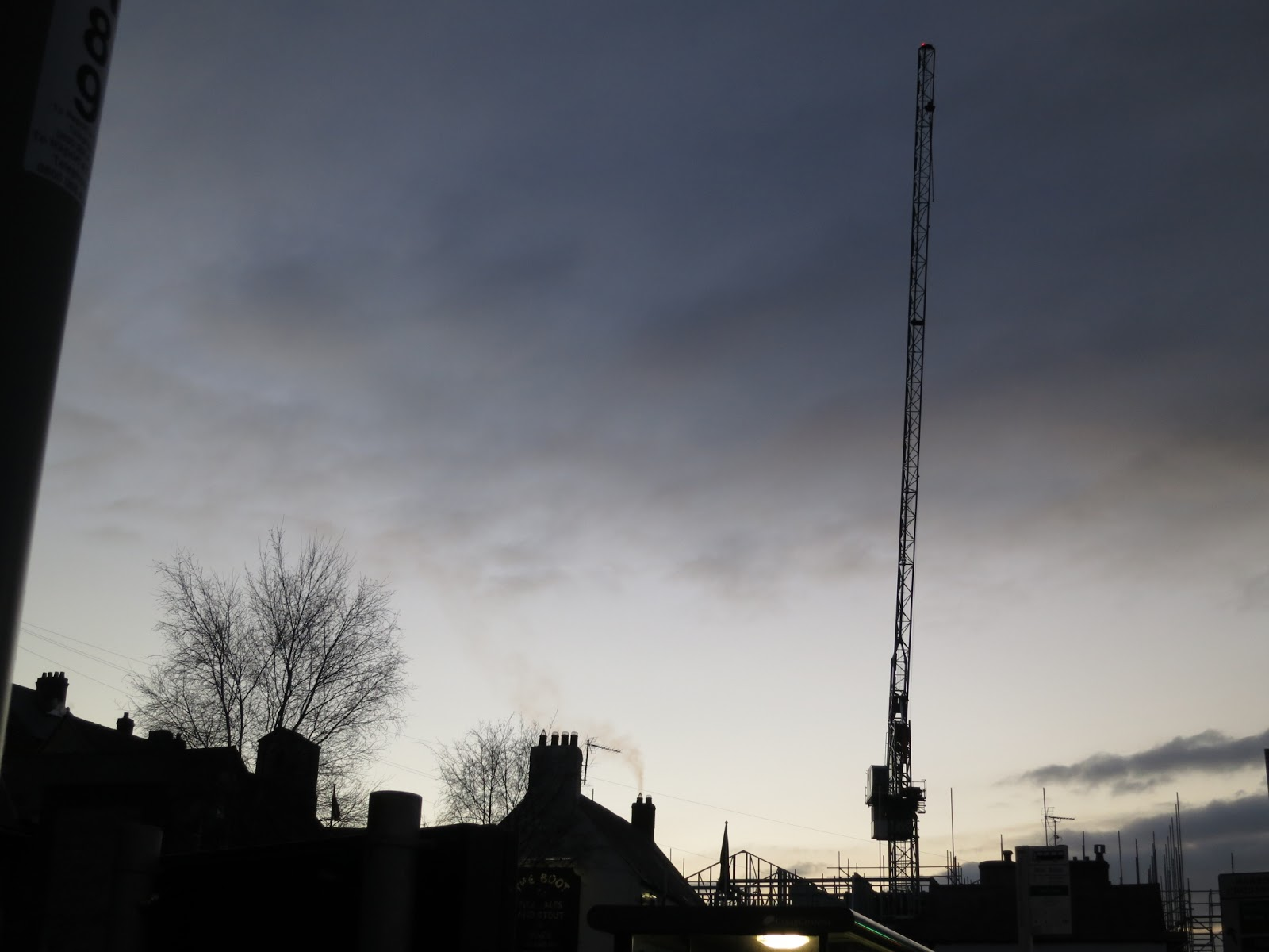 Evening. Silhouettes of crane on building site, smoke from pub chimney and winter trees