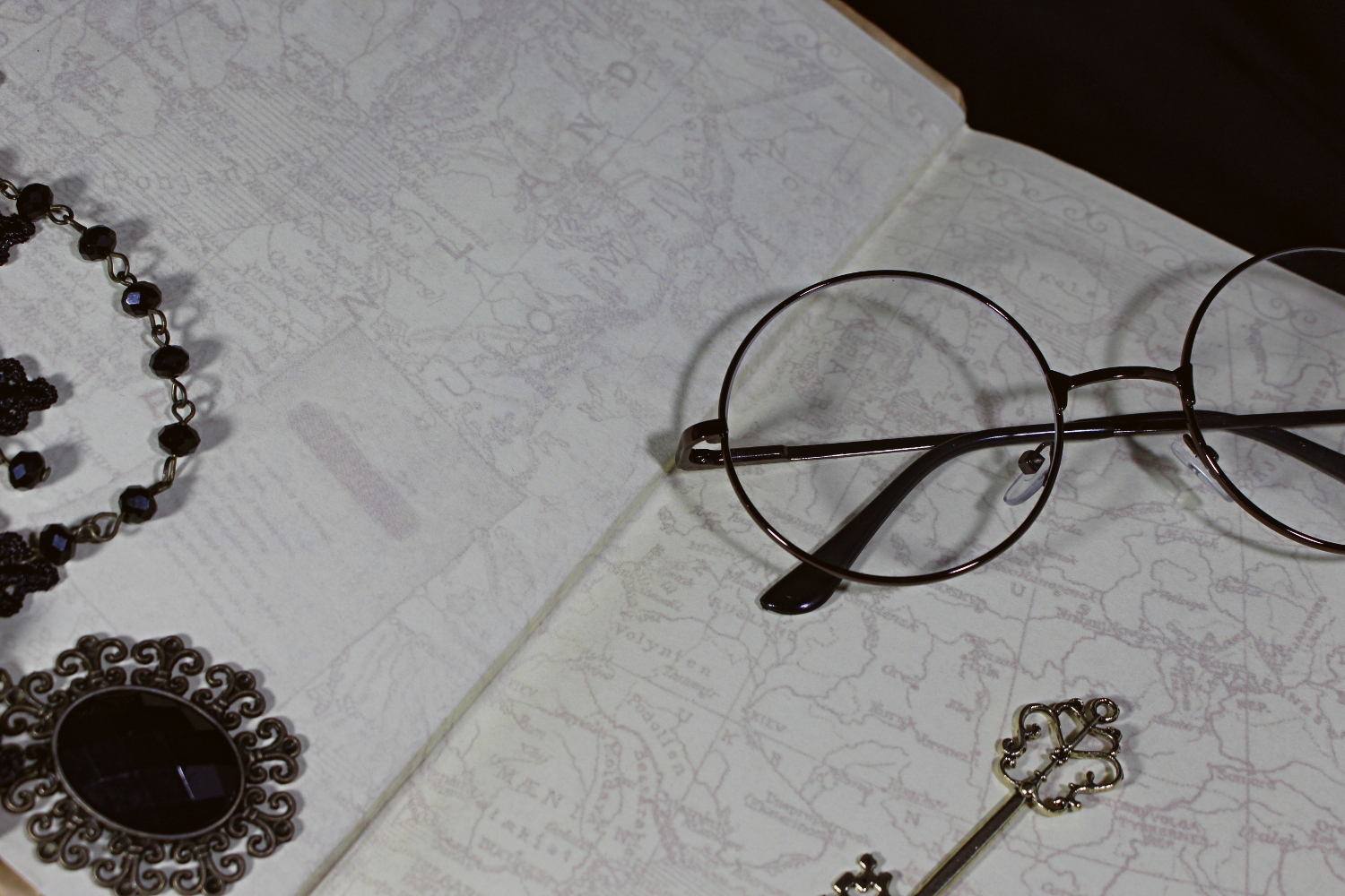 a close up image of round glasses laying on an opened book
