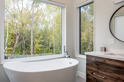 real estate photography view of a stand alone bath tub with two bright windows onto forest
