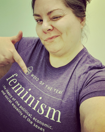 image of me from mid-torso up, wearing a purple t-shirt with the definition of FEMINISM on it, pointing at the shirt and winking at the camera; I've got contacts in and my hair up in a messy bun