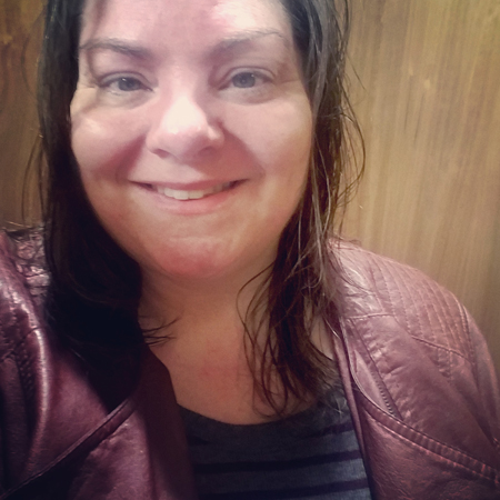 image of me in a closed, wood-walled changing stall at the gym, wearing contact lenses, a striped shirt, and a burundy moto jacket; I have wet hair and am smiling at the camera