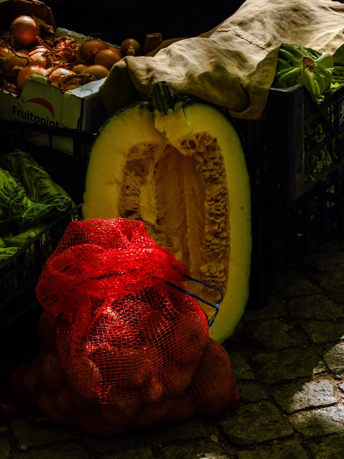 Half a giant yellow pumpkin on display with onions in bags and boxes at a market in Porto, Portugal.