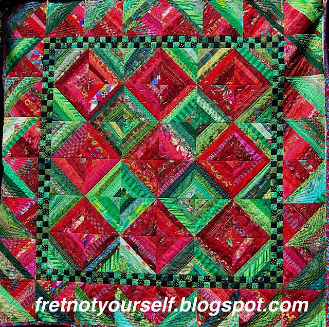 String quilt of green and red fabric strings.