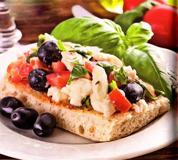 Хлеб пшеничный - 2 кусочка; Сыр твердый - 100 г; Помидор - 2 шт.; Чеснок - 2 зубчика; Оливковое масло - 2 ст.л; Маслины - 50 г; Перец черный молотый, соль, зелень - по вкусу; Листья салата, базилика - для подачи;