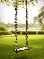 Bir ağaca kurulmuş çiçek ve sarmaşıklarla süslenmiş salıncak