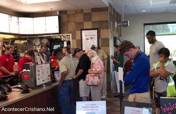 Empleados y clientes de restaurante orando