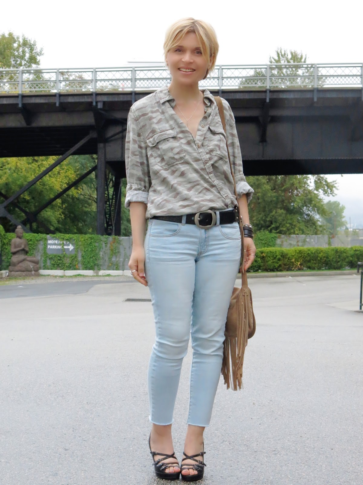 Settling in:  faded skinny jeans, camo shirt, and a fringy crossbody bag