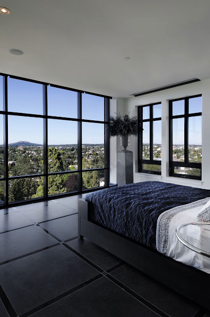 Picture of modern black and white bedroom with glass walls and the view of green hills
