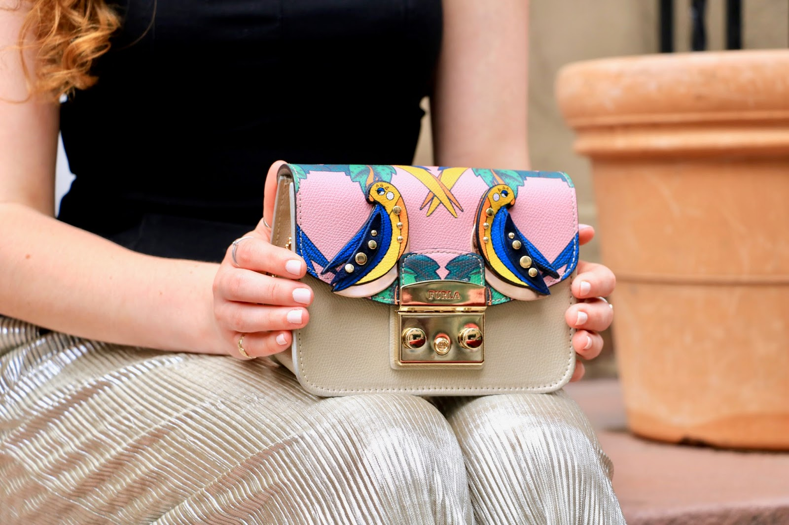 nyc fashion blogger Kathleen Harper holding a Furla mini bag crossbody