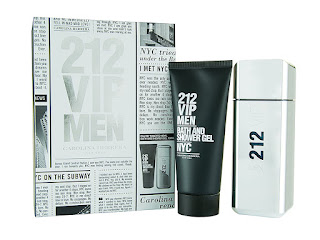 A thick silver metallic tin with a black interior with 212 VIP Men engraved into the left hand side of the tin with Caroina Herrera on the front in smaller black font with a tall rectangular silver metalic bottle with a square silver lid with 212 VIP Men in black medium sized font next to a triangular long black bottle with 212 VIP Men Bath and Shower Gel NYC in white font with Carolina Herrera in smaller white font on a white background.