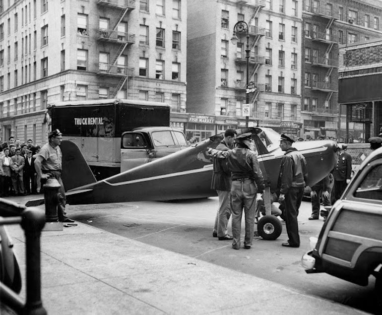 Pilot Thomas Fitzpatrick, speaking to police, in front of the small airplane he stole and landed on a street in Manhattan, blocking traffic, after a bar bet. 1956. The Best Bet EVER and other stories of pilots. marchmatron.com