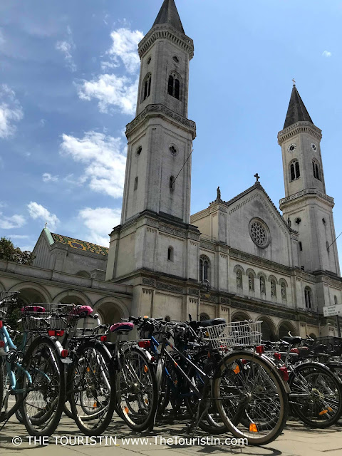 A row of bicycles parked in front of a white neo-Romanesque style church.