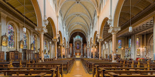 Interior view of the white arches, goldtone pews and stained glass windows of Whitefriar Street Church in Dublin, Ireland