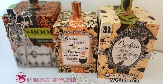 This is a picture of three paper-crafted block pumpkins decorated with Halloween stickers.