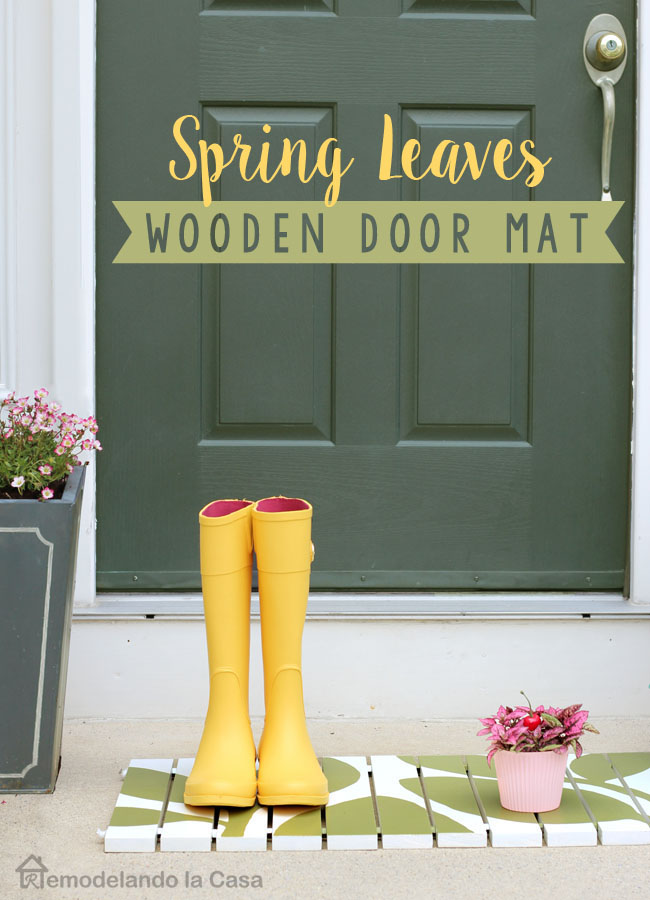 green front door with wooden door mat and flower