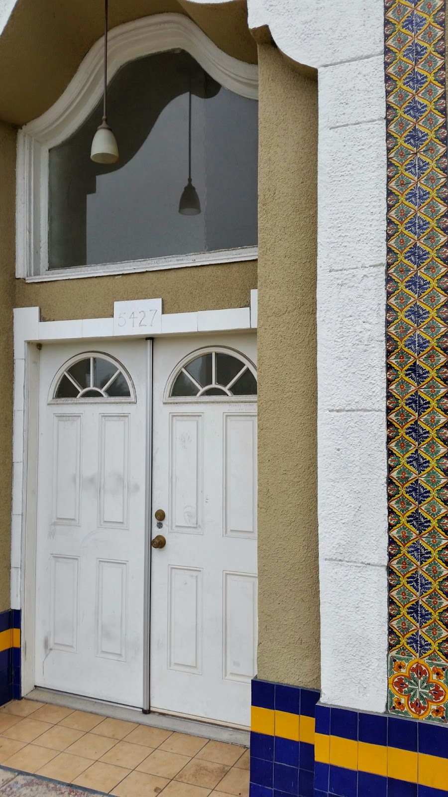 Tile ribbons cascade from the Spanish Baroque window details.