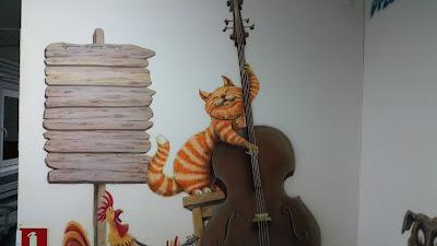 Malowanie klasy szkolnej, kot grający na kontrabasie, mural w sali muzycznej, aranżacja klasy muzycznej, malowanie murali 3D w szkołach, klasach