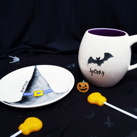 a white mug with a black bat and font reading 'spooky' sits next to a white saucer featuring a witches hat and text reading 'bewitching', against a black backdrop with halloween themed orange lollipops and pin badges