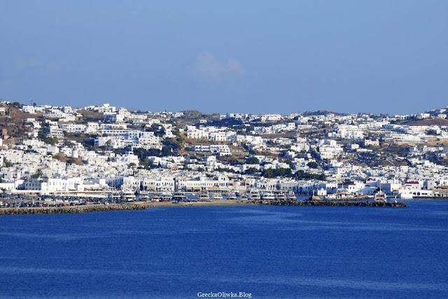 Białe kubistyczne budynki Mykonos na tle błękitnego niebia i lazurowego morza. Cyklady Grecja.