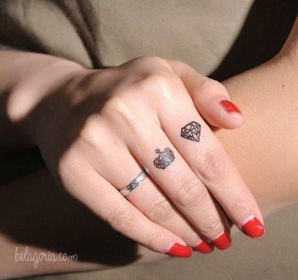 Un tatuaje en los dedos de diamante y corona de una chica