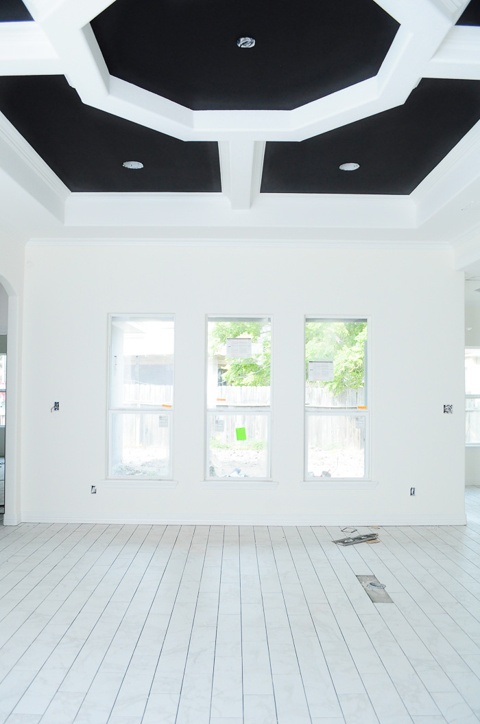 Marble look tile flooring in a living room with alabaster walls and a tricorn black tray ceiling. | via monicawantsit.com