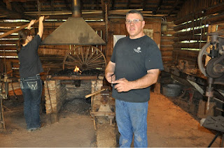 man in pioneer blacksmith shed